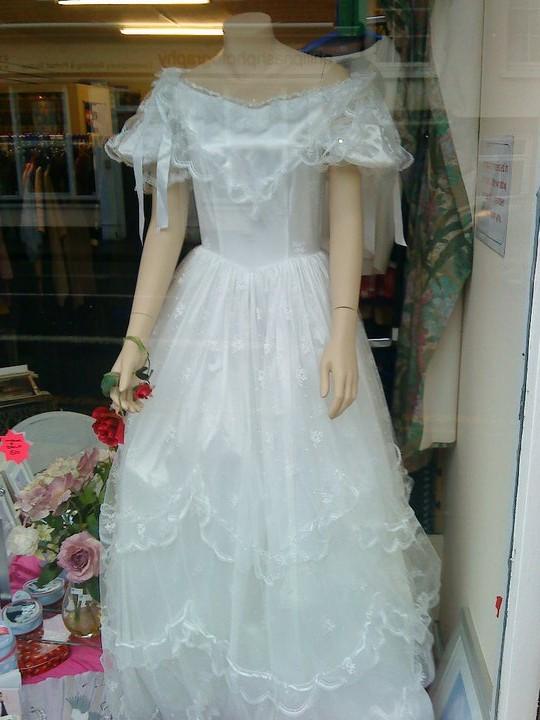 Joke image of a horrific wedding dress in a charity shop